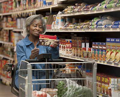 Older woman in wheel chair reading food label